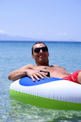 Young man in water on inflatable life ring