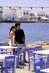 Couple by seaside restaurant tables