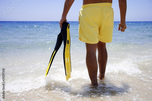 Lower half of man in water with flippers on the beach