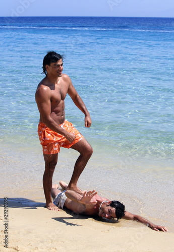 Man stepping on friend on the beach