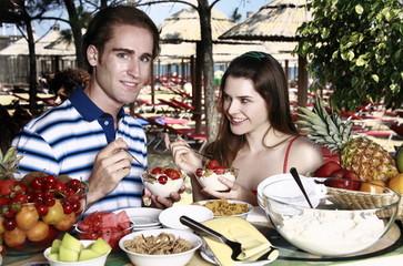 Young adult couple eating breakfast
