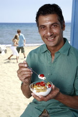 Male mature adult eating breakfast at beach
