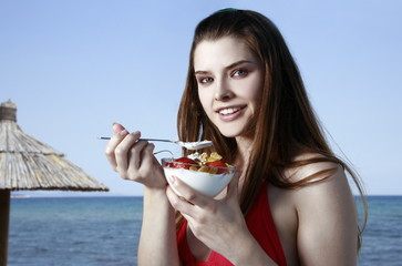 Female young adult eating fruit and yogurt on beach