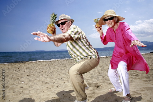 Senior couple with pineapples on the beach