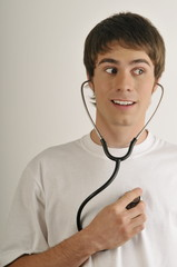 """""""Young male adult;listening to his heart with stethoscope"""""""