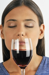 Female young adult smelling a glass of red wine