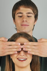 Young adult male holding hands over woman's eyes