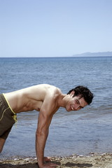 Young adult male doing pushups on beach