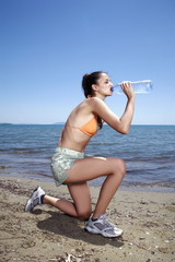 Athletic female young adult drinking bottled water on beach