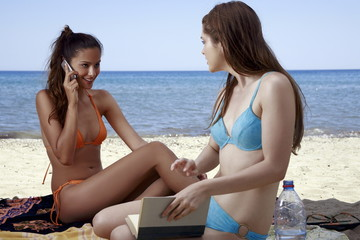 Two female young adults reading and talking on cell phone on beach
