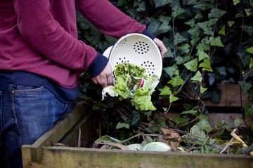 A man emptying vegetable peelings onto a compost heap