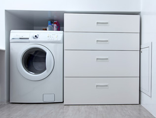Washing machine and white wardrobe in the modern bathroom.