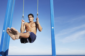 Man on a beach working out on exercise rings apparatus