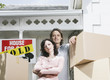 Man and woman with cardboard boxes standing in front of house with sold sign