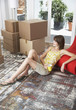 Woman sitting on hardwood floor with mug and cardboard boxes smiling