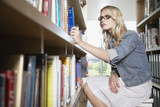 Young Woman in library at school with books