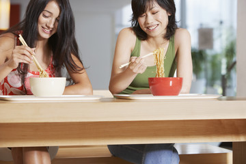 Young Women eating bowl of noodles with chopsticks in cafeteria