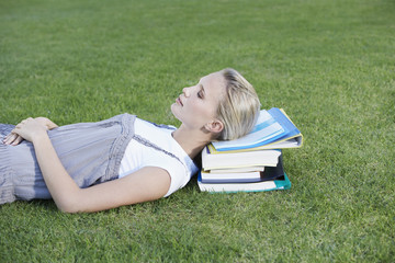 Young Woman laying down in grass on books