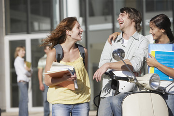 Young Man and women outdoors with scooter and helmet
