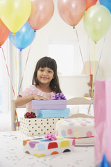 Girl with birthday presents and balloons