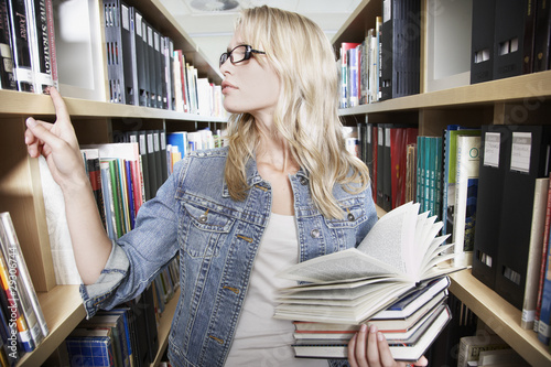 Teenage girl in library at school with books