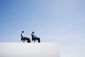 Two businessmen on wall with office chairs in a row