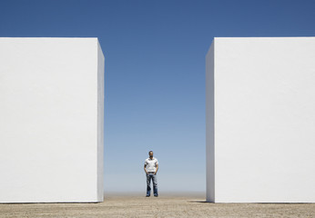 Man standing behind two walls outdoors