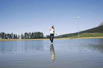 Woman dancing on water with surveillance camera and trees
