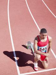 Racer at start line on track kneeling