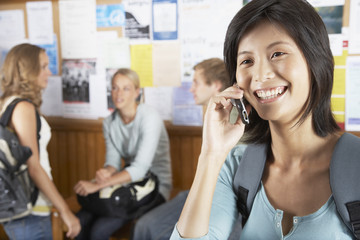 Woman on a cellular phone with three people in the background