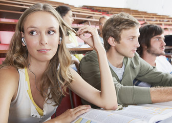 A female wearing earbuds in a classroom with four students in the background
