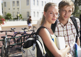 A young man and woman standing by a bike rack