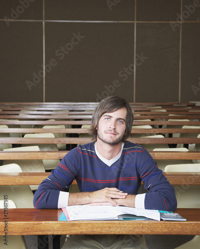 A young male student sitting in a classroom alone