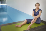 Woman sitting on a yoga mat smiling