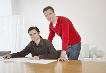Two businessmen leaning over a table with city model behind them