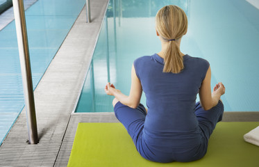 Woman doing yoga by an indoor pool