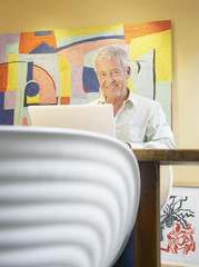 Man on laptop at a table in modern home