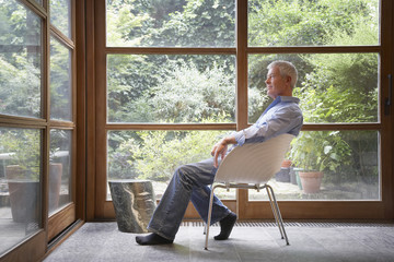 Man sitting by large windows in modern home