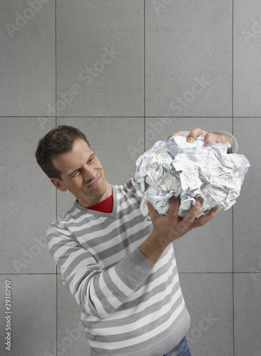 Man squeezing large ball of paper