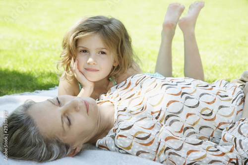 Woman and young girl lying down on blanket outdoors
