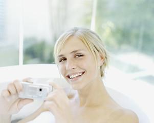 A woman in a bathtub with a camera