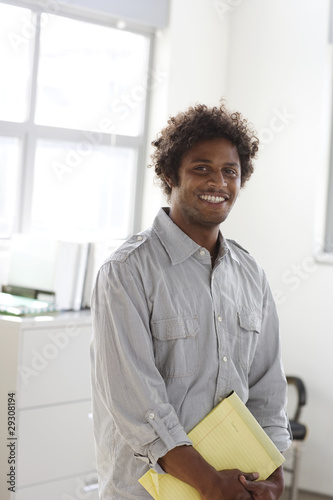 Businessman holding notepad in office