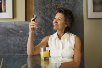Woman sitting at a table with orange juice and a mobile phone