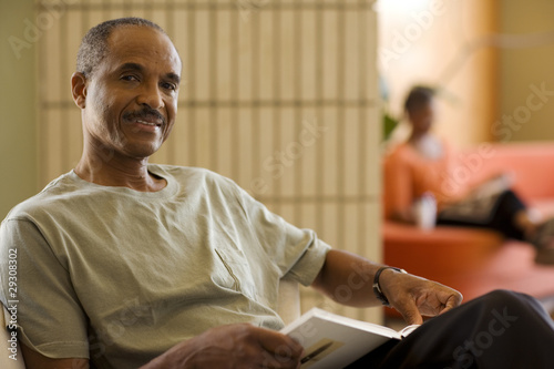 Man with book in living room with woman in background reading