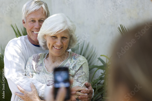 Couple having picture taking with camera phone outdoors