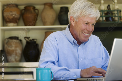 Man at laptop with mug smiling