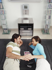 Couple lying on rug holding hands