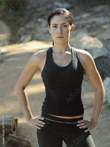 A woman standing in work out gear in the woods
