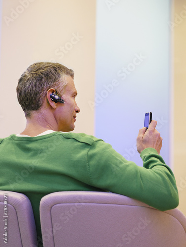 man sitting with headset and mobile phone