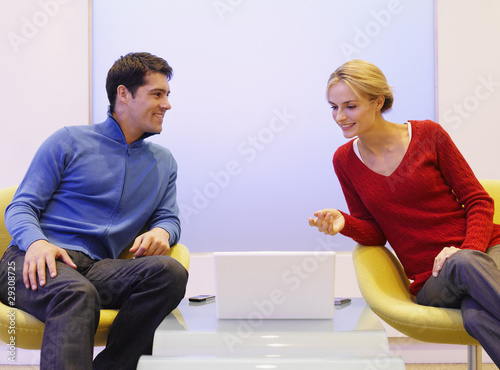 Man and woman sitting in chairs with laptop between them